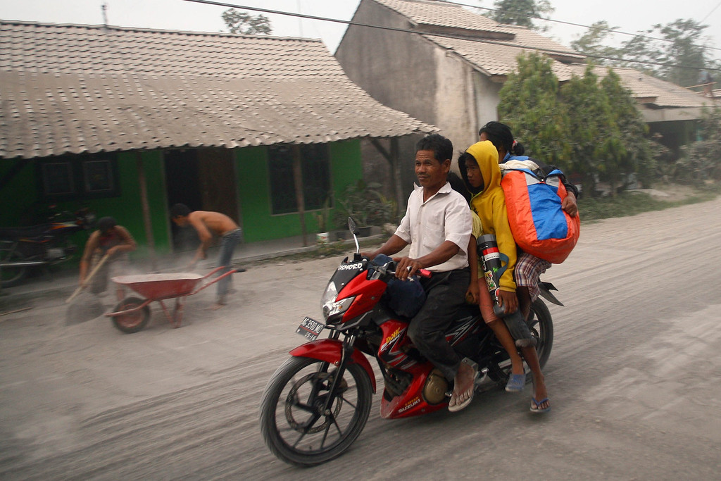. A family fleeing on a motorcycle during mass evacuation pass the ash covered village of Kediri in East Java province on February 14, 2014 following the eruption of Mount Kelud volcano.  AFP PHOTO / JUNI KRISWANTO/AFP/Getty Images