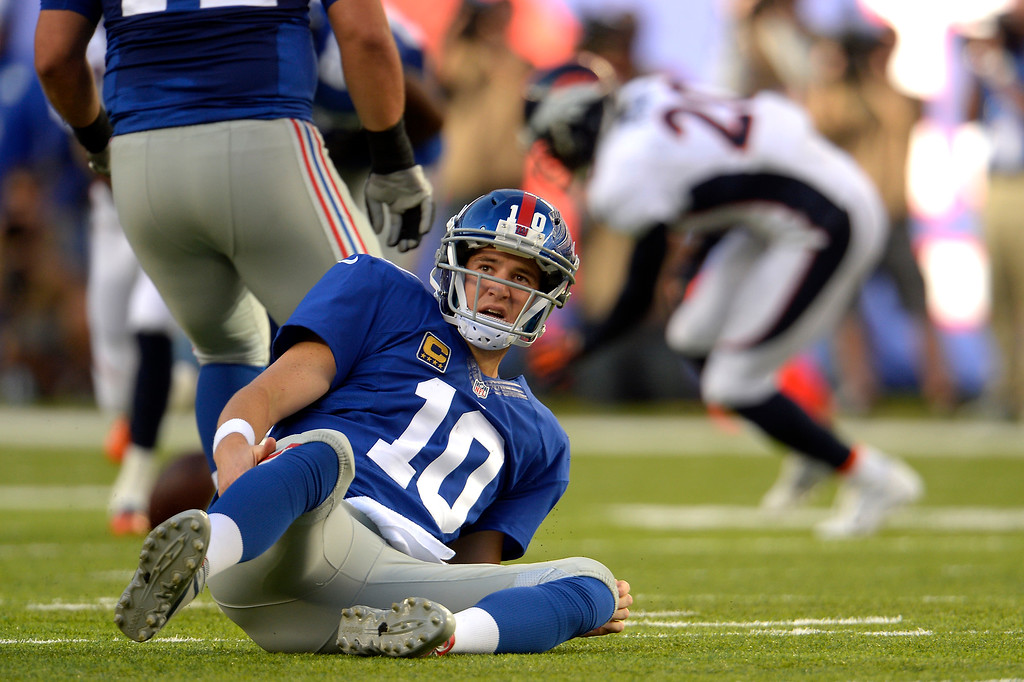 . Eli Manning (10) of the New York Giants was hit as he released the ball by defensive end Malik Jackson (97) of the Denver Broncos on third down at METLIFE Stadium. The pass was incomplete September 15, 2013 East Rutherford, NJ. (Photo By Joe Amon/The Denver Post)