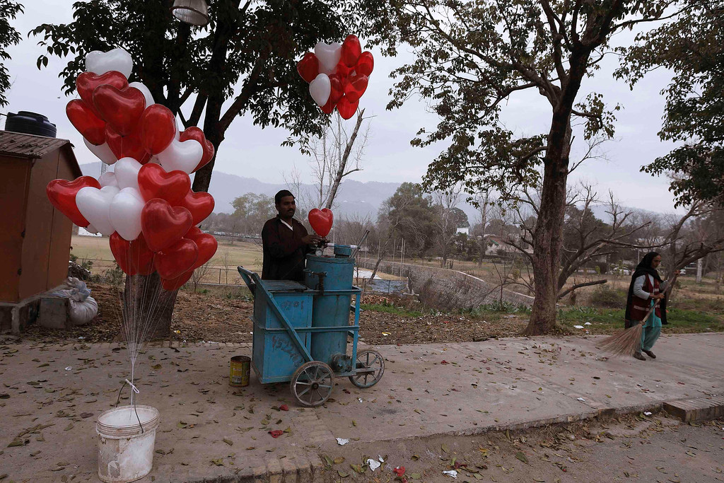 . A street seller inflates a heart-shaped balloon while a street cleaner sweeps on Valentine\'s Day in Islamabad February 14, 2013. REUTERS/Zohra Bensemra