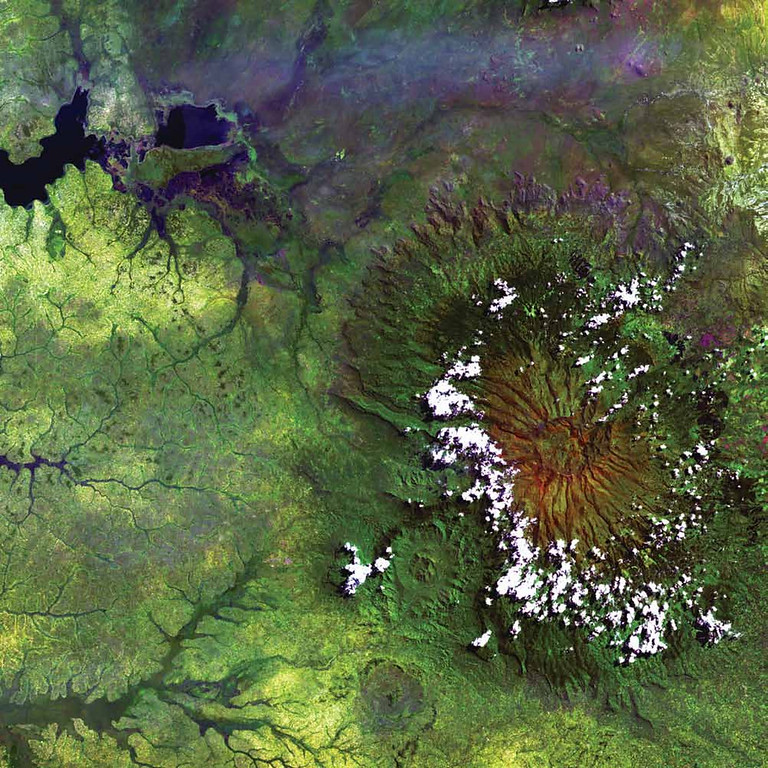 . Mount Elgon, Kenya and Uganda Clouds dot the high rim of Mount Elgon�s massive caldera in this Landsat 5 image from 1984. As the oldest and largest solitary volcano in Africa, Mount Elgon straddles the border between Uganda and Kenya and is protected on both sides by national parks. Named Ol Doinyo Ilgoon by the Maasai, this long-extinct volcano has an intact caldera about 6,500 meters across and consists of five major peaks over a distance of 4,100 meters. In the image, the lush green that surrounds the volcano shows the fertility of the rich volcanic soil at the lower elevations. The upper left corner shows one of the arms of the large shallow lake complex of Lake Kyoga.   NASA
