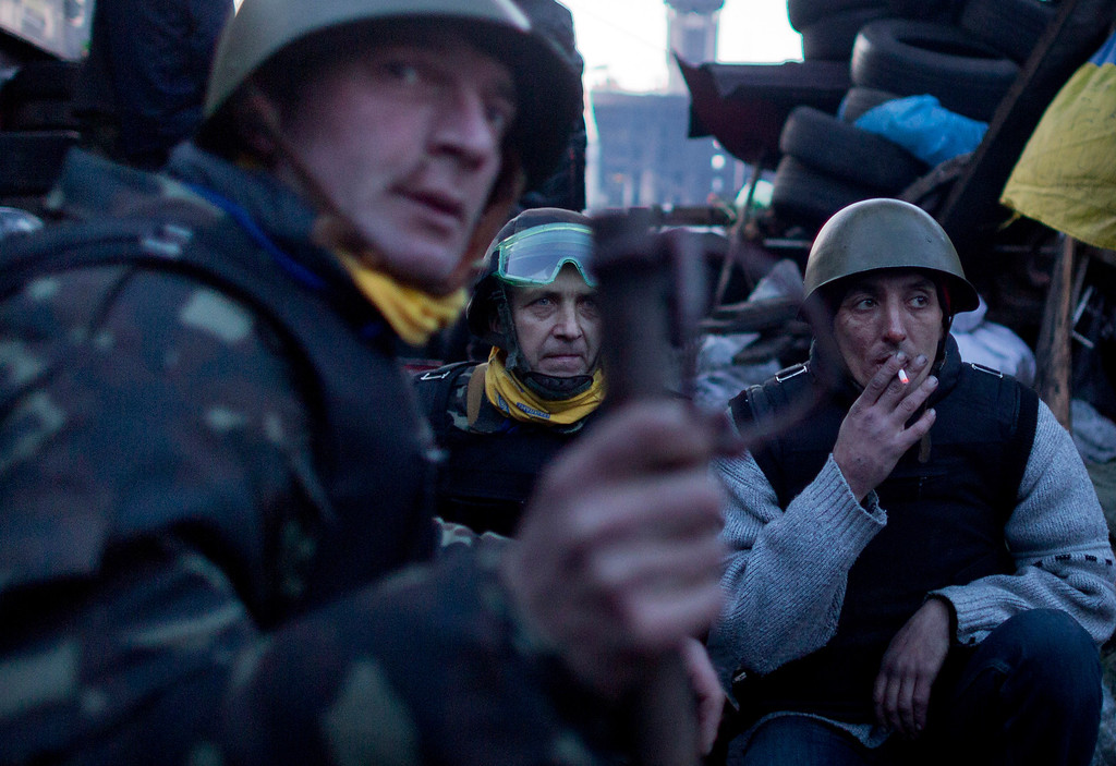 . Anti-government protesters man a barricade in central Kiev, Ukraine, Friday, Feb. 21, 2014.  European officials say Ukrainian protesters have agreed to a deal with Ukraine\'s president on defusing a deadly political crisis. Earlier Friday President Viktor Yanukovych announced early elections and promised to invite the opposition into the government. (AP Photo/Darko Bandic)
