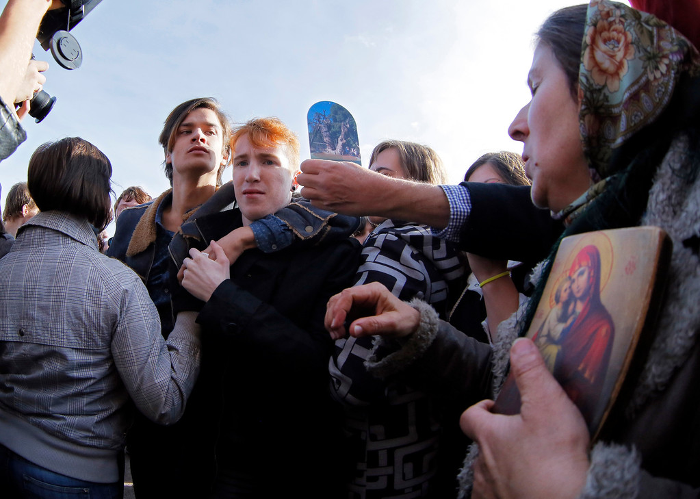 . Gay rights activists are opposed by anti-gay protesters during an authorized gay rights rally in St. Petersburg, Russia, Saturday, Oct. 12, 2013. A gay rights rally in St. Petersburg has ended in scuffles after several dozen protesters were confronted by about 200 conservative and religious activists. The police standing nearby waited until clashes broke out between the two groups before intervening. According to Russian news agencies, the police detained 67 people from both sides. (AP Photo/Dmitry Lovetsky)