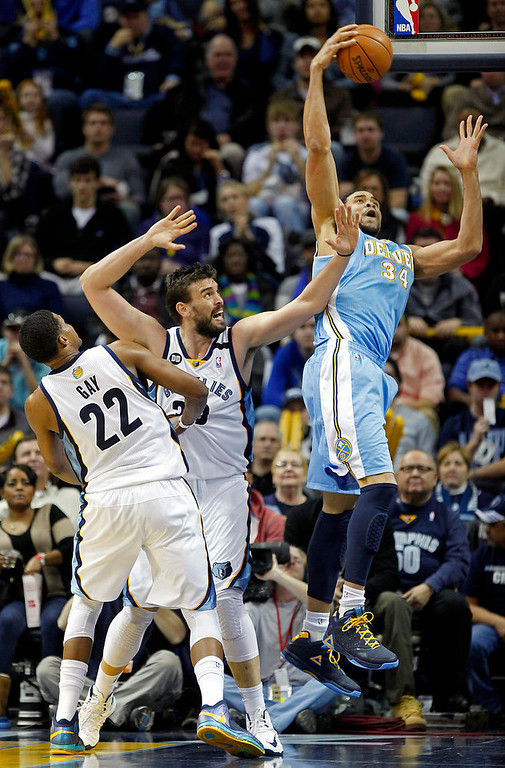 . Denver Nuggets center JaVale McGee (34) goes to the basket against Memphis Grizzlies Marc Gasol, center, of Spain, and Rudy Gay (22) in the second half of an NBA basketball game on Saturday, Dec. 29, 2012, in Memphis, Tenn. The Grizzlies won 81-72. (AP Photo/Lance Murphey)
