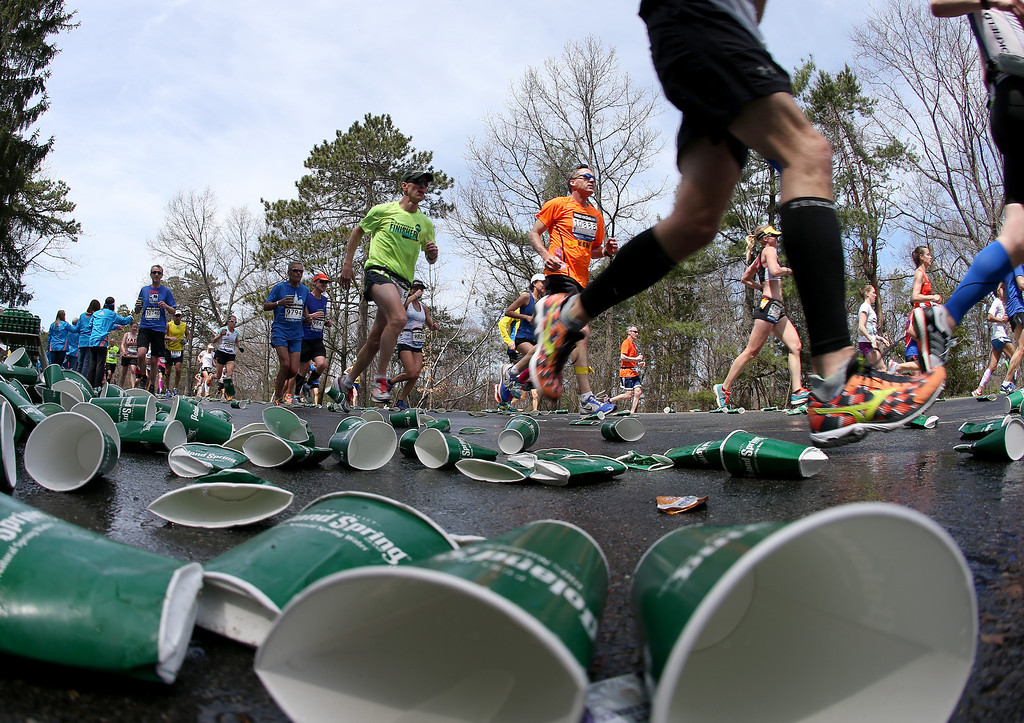 . Runners pass discarded cups after a water station during the 118th Boston Marathon Monday, April 21, 2014 in Wellesley, Mass. (AP Photo/Mary Schwalm)