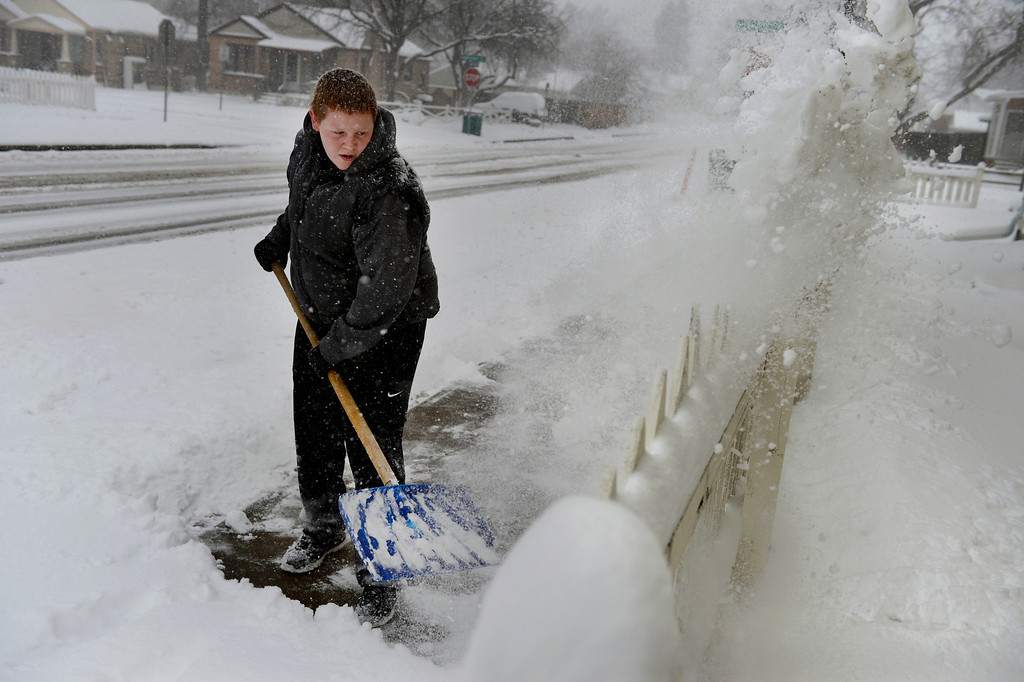 . LITTLETON, CO. - MARCH 23: Zack Hughson, 15, shovels the sidewalk outside a neighbors home in Englewood, CO March 23, 2013. The Saturday forecast calls for snow accumulation of 9 to 12 inches with highs in the lower to mid 20s. (Photo By Craig F. Walker/The Denver Post)