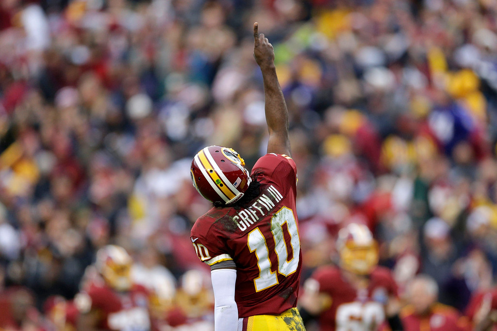 . Washington Redskins quarterback Robert Griffin III reacts to his touchdown pass to wide receiver Josh Morgan during the first half of an NFL football game against the Baltimore Ravens in Landover, Md., Sunday, Dec. 9, 2012. (AP Photo/Patrick Semansky)