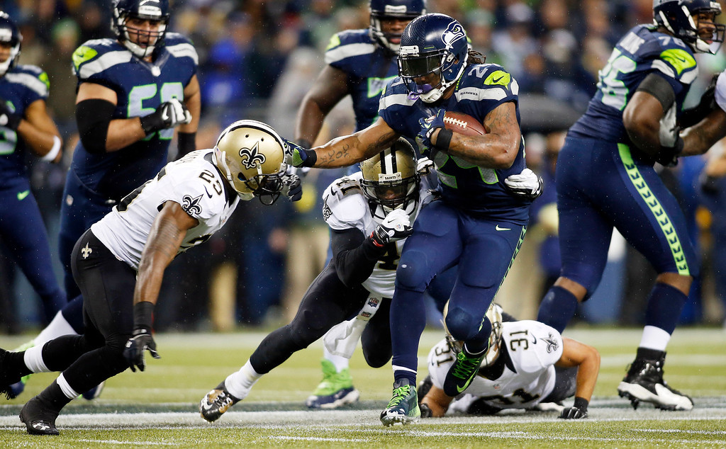 . Seattle Seahawks running back Marshawn Lynch (24) pushes off New Orleans Saints\' Rafael Bush, left, in the first half of an NFL football game Monday, Dec. 2, 2013, in Seattle. (AP Photo/John Froschauer)