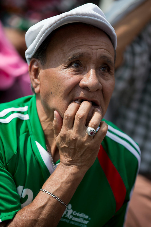 . A Mexico soccer fan watches his team\'s World Cup soccer match with Cameroon on giant television screens in Mexico Cityís main square, the Zocalo, Friday, June 13, 2014. (AP Photo/Rebecca Blackwell)