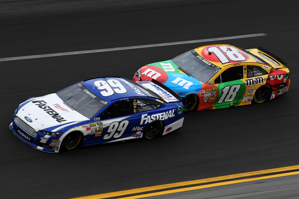 . Carl Edwards, driver of the #99 Fastenal Ford, leads Kyle Busch, driver of the #18 M&M\'s Toyota, during the NASCAR Sprint Cup Series Daytona 500 at Daytona International Speedway on February 24, 2013 in Daytona Beach, Florida.  (Photo by Todd Warshaw/Getty Images)