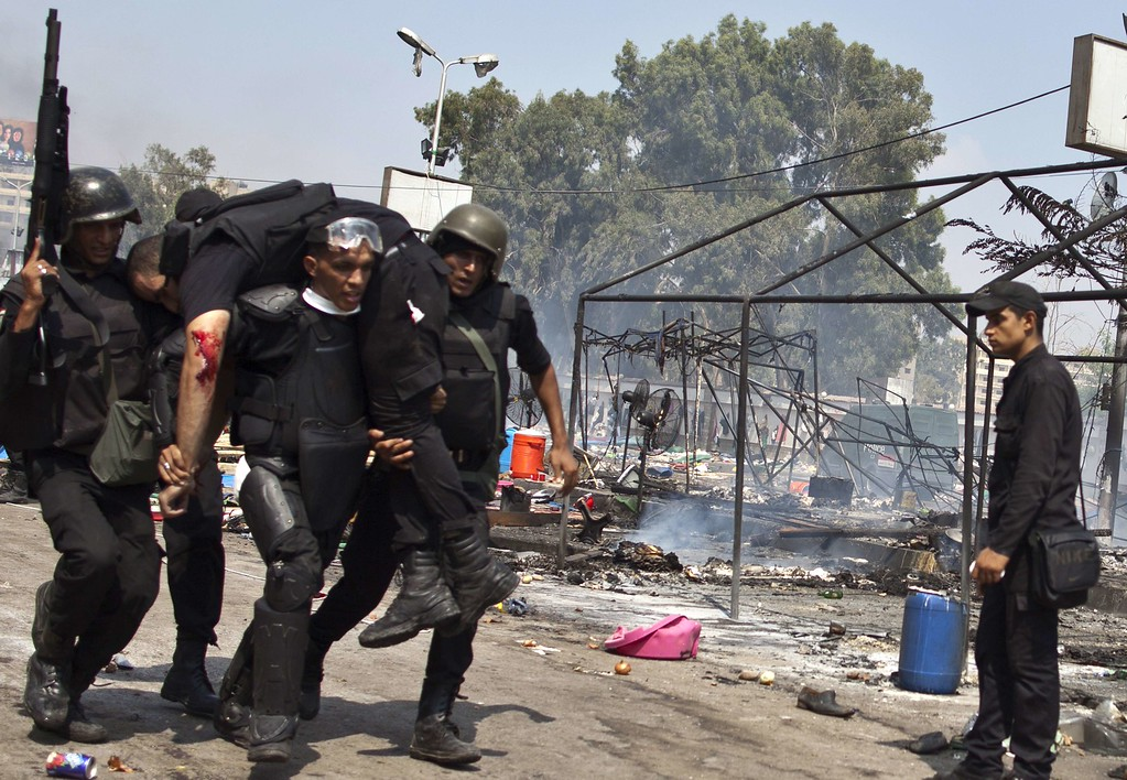 . Egyptian security forces carry an injured comrade after a police crackdown on a protest camp by supporters of ousted president Mohamed Morsi and members of the Muslim Brotherhood on August 14, 2013 near Cairo\'s Rabaa al-Adawiya mosque. AFP PHOTO / MAHMOUD  KHALED/AFP/Getty Images