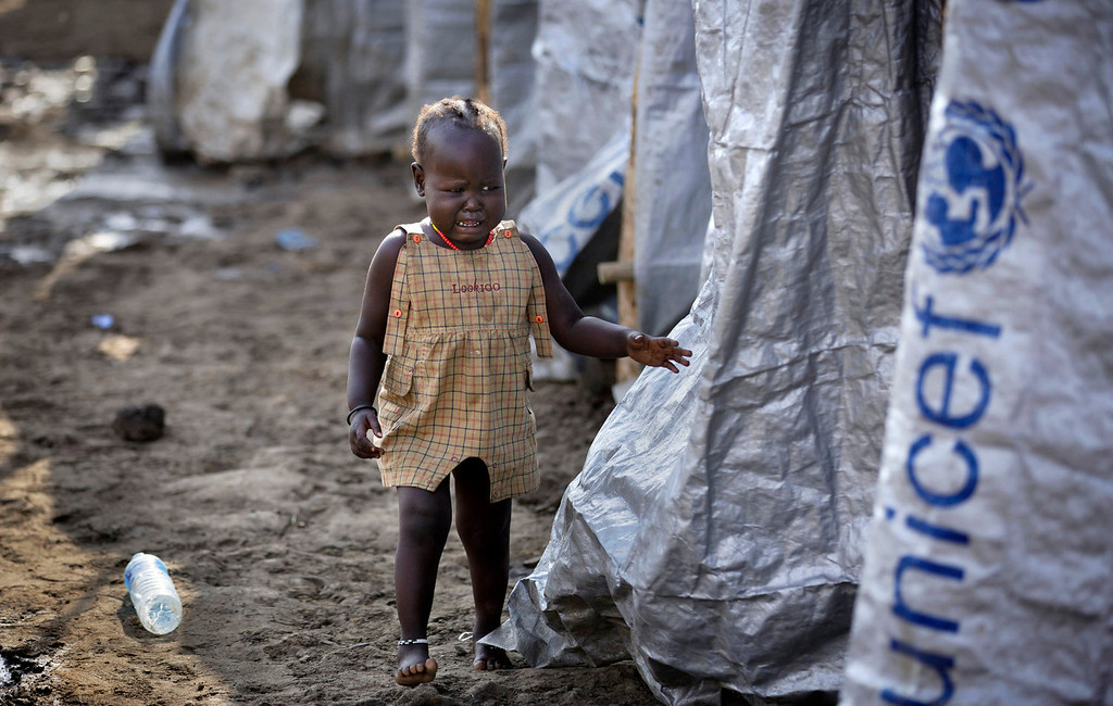 . A young displaced girl starts crying after the relative she was with disappears into a row of latrines, at a United Nations compound which has become home to thousands of people displaced by the recent fighting, in the capital Juba, South Sudan Sunday, Dec. 29, 2013. Some 25,000 people live in two hastily arranged camps for the internally displaced in Juba and nearly 40,000 are in camps elsewhere in the country, two weeks after violence broke out in the capital and a spiralling series of ethnically-based attacks coursed through the nation, killing at least 1,000 people. (AP Photo/Ben Curtis)