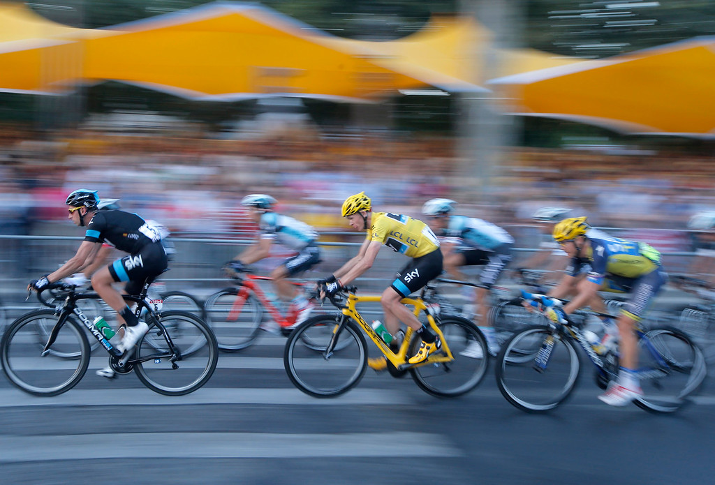 . Christopher Froome of Britain, wearing the overall leader\'s yellow jersey, center, rides during the 21st and last stage of the 100th edition of the Tour de France cycling race over 133.5 kilometers (83.4 miles) with start in Versailles and finish in Paris, France, Sunday July 21 2013.  (AP Photo/Laurent Cipriani)