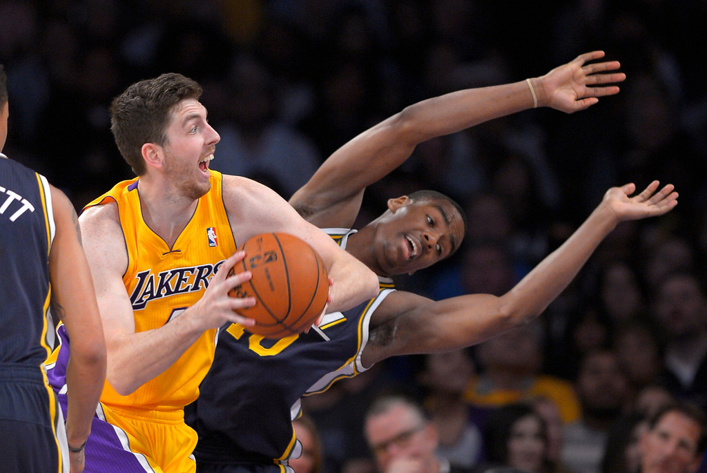. Los Angeles Lakers forward Ryan Kelly, left, looks for a shot as Utah Jazz guard Alec Burks falls during the first half of an NBA basketball game, Friday, Jan. 3, 2014, in Los Angeles. (AP Photo/Mark J. Terrill)