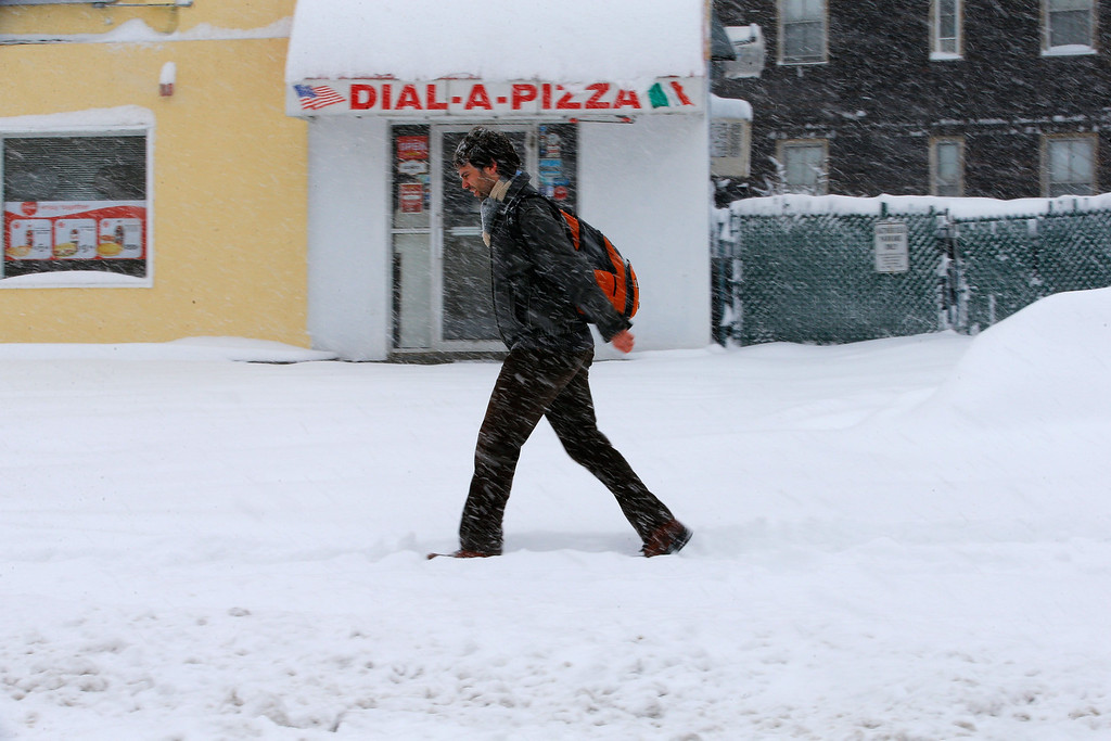 . A man walks through snow-covered streets in Somerville, Massachusetts March 8, 2013 as a slow-moving winter storm brought a combination of snow, rain and high winds to the northeast U.S. after moving through the mid-Atlantic states earlier in the week.    REUTERS/Brian Snyder