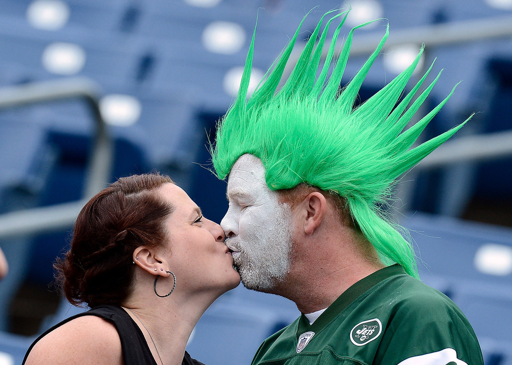 . New York Jets fans Ana Hall and Rick Martin kiss as they watch players warm up before an NFL football game between the Jets and the Tennessee Titans on Sunday, Sept. 29, 2013, in Nashville, Tenn. (AP Photo/Mark Zaleski)