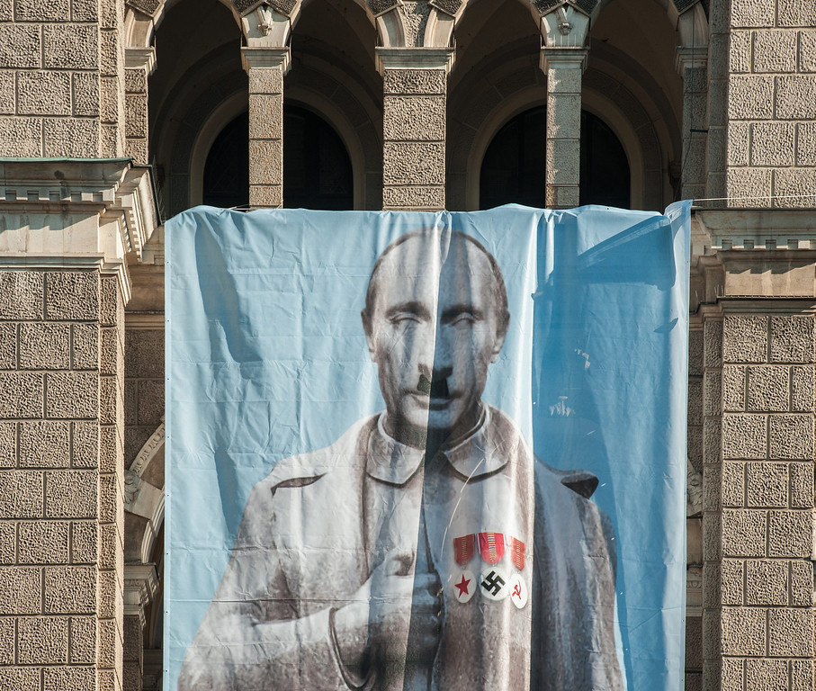 . A huge canvas caricaturing Russian President Vladimir Putin was unveiled by the Dekomunizace (Decommunisation) civic association on the seat of the Town Hall in Liberec, Czech Republic, on Tuesday, March 11, 2014. The association protests against the steps taken by the strengthening Russian dictatorship in Crimea. The canvas is hanging right above a monument to the minimally nine people who died in Liberec when Soviet tanks occupied the country in 1968 to crush the Prague Spring reform movement. (AP Photo/CTK, Radek Petrasek)