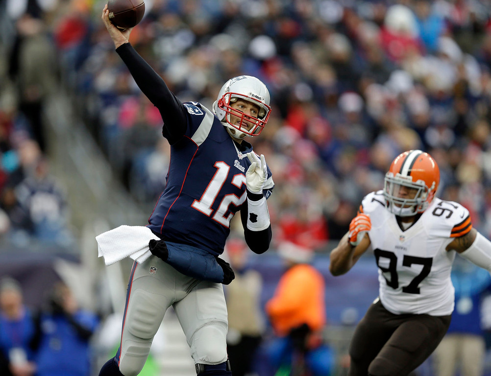 . New England Patriots quarterback Tom Brady (12) passes in front of Cleveland Browns linebacker Jabaal Sheard (97) in the first quarter of an NFL football game on Sunday, Dec. 8, 2013, in Foxborough, Mass. (AP Photo/Steven Senne)
