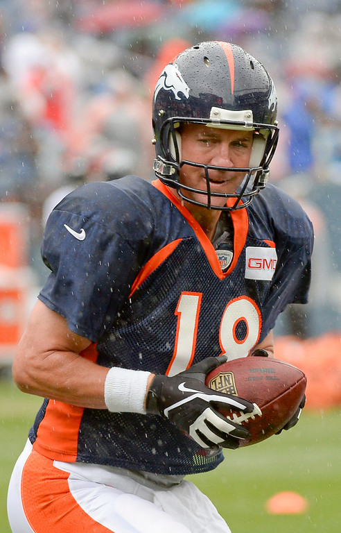 . Denver Broncos quarterback Peyton Manning (18) wears the glove during a rain day on day six of the Denver Broncos 2014 training camp July 30, 2014 at Sports Authority Field at Mile High Stadium.  (Photo by John Leyba/The Denver Post)