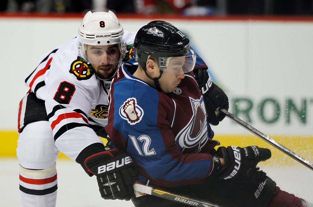 . Chicago Blackhawks defenseman Nick Leddy, left, is called for a holding penalty as he tries tostop Colorado Avalanche right wing Chuck Kobasew in the first period of an NHL hockey game in Denver, Friday, March 8, 2013. (AP Photo/David Zalubowski)