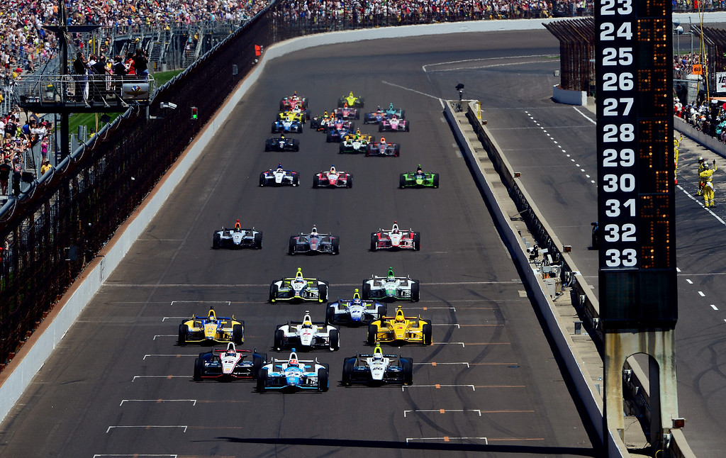 . Will Power of Australia, driver of the #12 Verizon Team Penske Chevrolet Dallara, James Hinchcliffe, driver of the #27 Andretti Autosport Honda Dallara, and Ed Carpenter, driver of the #20 Fuzzy\'s Vodka / Ed Carpenter Racing Chevrolet Dallara, lead the field to start the 98th running of the Indianapolis 500 at Indianapolis Motorspeedway on May 25, 2014 in Indianapolis, Indiana.  (Photo by Robert Laberge/Getty Images)