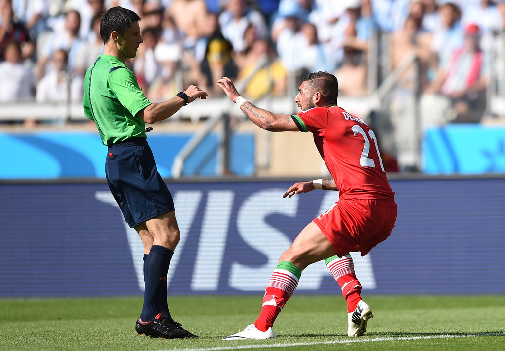 . Iran\'s forward Ashkan Dejagah (R) pleads with Serbian referee Milorad Mazic for a penalty during the Group F football match between Argentina and Iran at the Mineirao Stadium in Belo Horizonte during the 2014 FIFA World Cup in Brazil on June 21, 2014.  BEHROUZ MEHRI/AFP/Getty Images