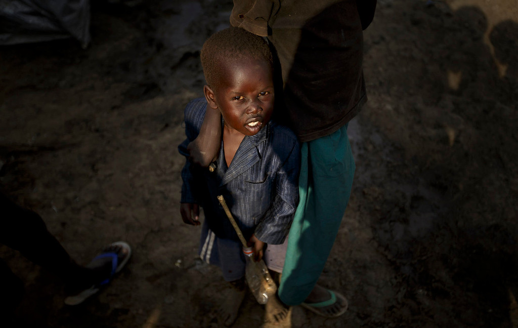 . A young displaced boy at a United Nations compound which has become home to thousands of people displaced by the recent fighting, in the capital Juba, South Sudan Sunday, Dec. 29, 2013. Some 25,000 people live in two hastily arranged camps for the internally displaced in Juba and nearly 40,000 are in camps elsewhere in the country, two weeks after violence broke out in the capital and a spiralling series of ethnically-based attacks coursed through the nation, killing at least 1,000 people. (AP Photo/Ben Curtis)