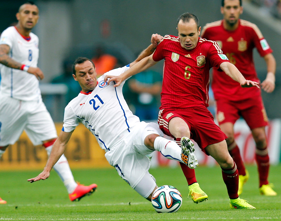 . Chile\'s Marcelo Diaz holds on to Spain\'s Andres Iniesta during the group B World Cup soccer match between Spain and Chile at the Maracana Stadium in Rio de Janeiro, Brazil, Wednesday, June 18, 2014.  (AP Photo/Frank Augstein)