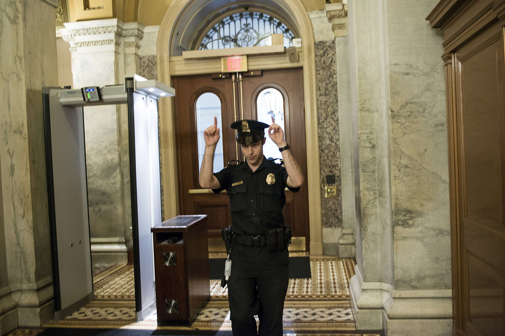 ". A Capitol Police Officer directs people away from a door on Capitol Hill October 3, 2013 in Washington, DC. The US Capitol was placed on security lockdown Thursday after shots were fired outside the complex, senators said. ""Shots fired outside the Capitol. We are in temporary lock down,\"" Senator Claire McCaskill said on Twitter. Police were seen running within the Capitol building and outside as vehicles swarmed to the scene. AFP PHOTO/Brendan  SMIALOWSKI/AFP/Getty Images"