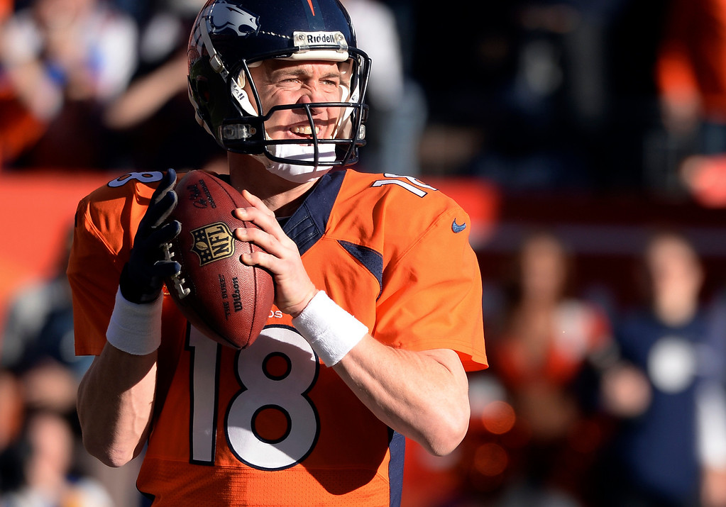 . Denver Broncos quarterback Peyton Manning (18) looks for a receiver during the third quarter against the New England Patriots in the AFC Championship game  at Sports Authority Field at Mile High in Denver on January 19, 2014. (Photo by Helen Richardson/The Denver Post)