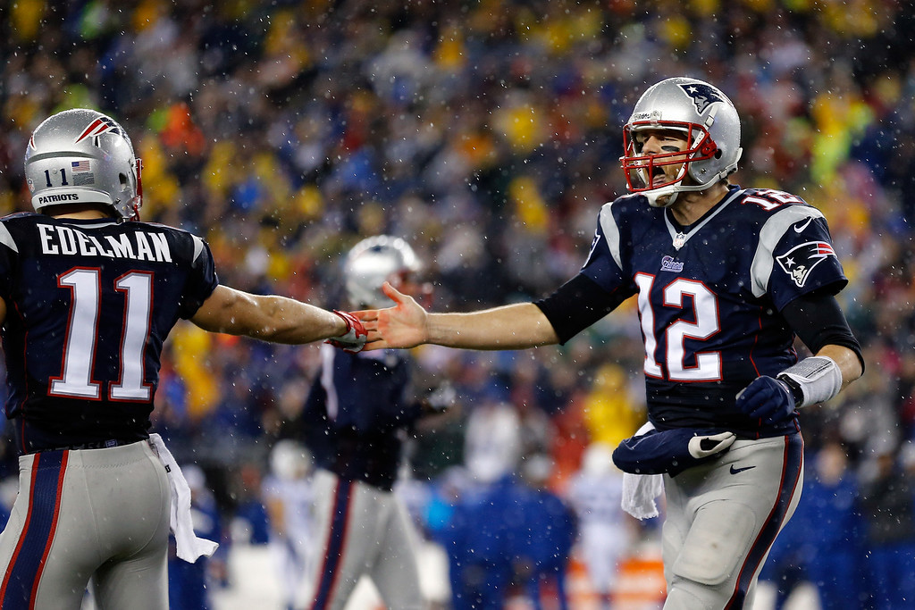 . FOXBORO, MA - JANUARY 11:  Tom Brady #12 of the New England Patriots reacts with teammate  Julian Edelman #11 after a play against the Indianapolis Colts during the AFC Divisional Playoff game at Gillette Stadium on January 11, 2014 in Foxboro, Massachusetts.  (Photo by Jim Rogash/Getty Images)