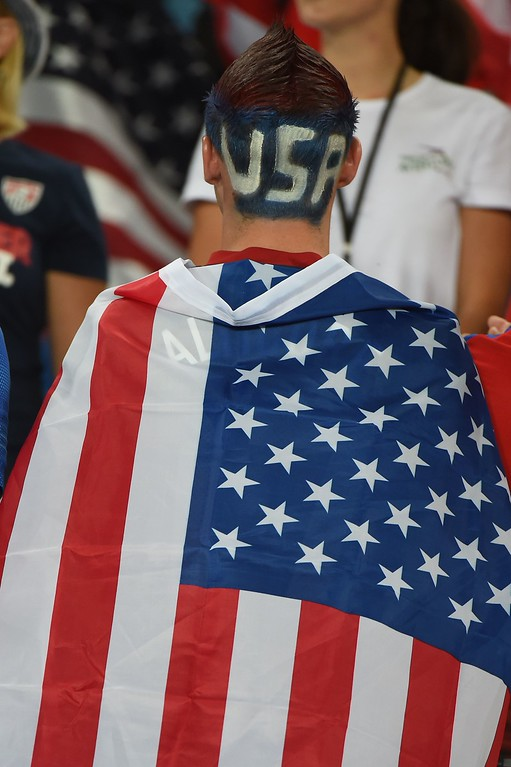 . A US fan wears a US flag before a Group G football match between Ghana and US at the Dunas Arena in Natal during the 2014 FIFA World Cup on June 16, 2014.  AFP PHOTO / EMMANUEL  DUNAND/AFP/Getty Images
