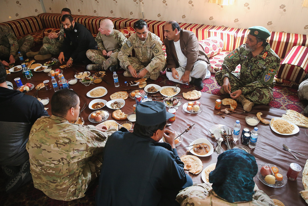 . PUL-E ALAM, AFGHANISTAN - MARCH 26:  U.S. Army soldiers and provincial leaders eat with Haji Niyaz Mohammad Amirii (R), provincial governor of Logar Province, following a shura in his office on March 26, 2014 in Pul-e Alam, Afghanistan. A shura is a meeting of community leaders. Security is at a heightened state throughout Afghanistan as the nation prepares for the April 5th presidential election.  (Photo by Scott Olson/Getty Images)