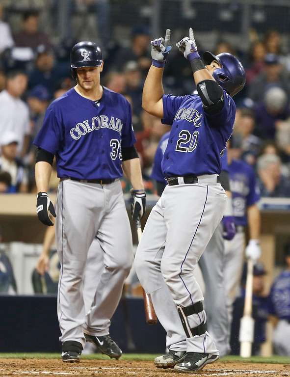 . Colorado Rockies\' Wilin Rosario points to heavens as he crosses home plate with a two-run homer against the San Diego Padres in the fifth inning of a baseball game Monday, April 14, 2014, in San Diego. (AP Photo/Lenny Ignelzi)