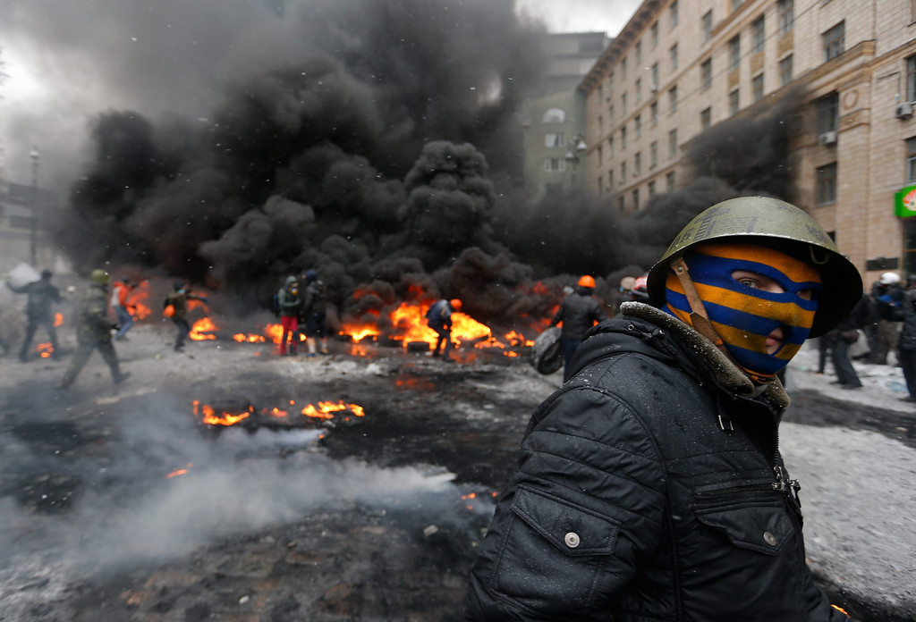. Protesters burn tires as they clash with riot police during an anti government protest in Kiev, Ukraine, 22 January 2014.   EPA/MAKSIM MARUSENKO