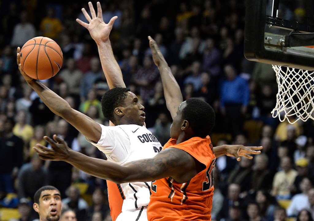 . Colorado\'s Jaron Hopkins goes for a dunk over Jarmal Reid during an NCAA game against Oregon State on Thursday, Jan. 2, at the Coors Event Center in Boulder.  Jeremy Papasso/ Camera