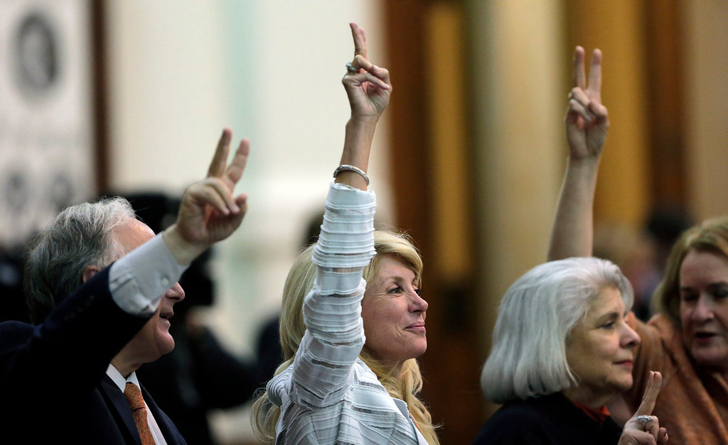 ". Sen. Wendy Davis, D-Fort Worth, center, holds up two fingers to signal a ""No\"" vote in the session where she filibustered an abortion bill in Austin, Texas on June 25, 2013. Hundreds of abortion rights activists ensured that the first special legislative session descended into chaos. Now, Texas Gov. Rick Perry has convened a second one and urged abortion opponents to respond with mobilizations of their own. (AP Photo/Eric Gay, File)"