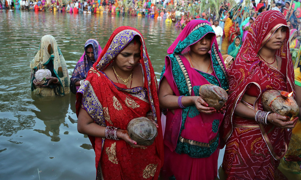 . Hindu devotees hold coconuts as they stand in water to perform rituals to the setting sun during Chhath Puja festival in Bangalore, India, Friday, Nov. 8, 2013.  (AP Photo/Aijaz Rahi)
