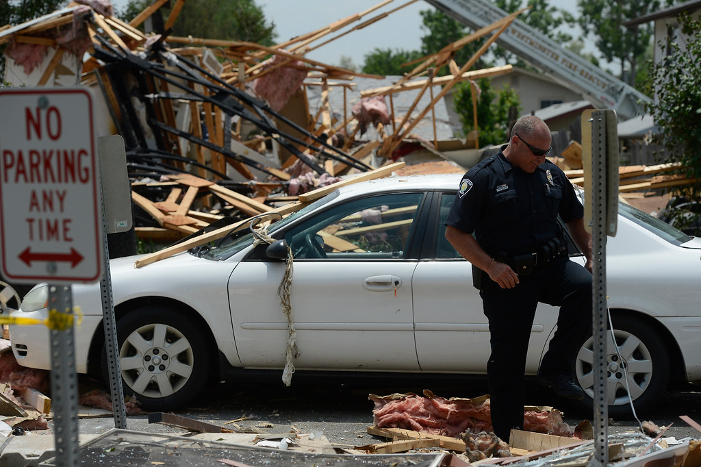 . A Westminster police officer steps over debris scattered at the scene of the  house explosion Thursday afternoon June 13, 2013.  (Photo By Andy Cross/The Denver Post)