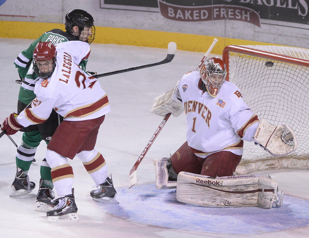 . DENVER, CO. - JANUARY 24:  North Dakota wing Drake Caggiula (9) blasted a shot past Denver goaltender Sam Brittain (1) for a goal in the first period. The University of Denver hockey team hosted North Dakota at Magness Arena Friday night, January 24, 2014. Photo By Karl Gehring/The Denver Post