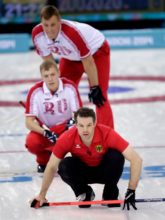 . Germanyís Felix Schulze, bottom, watches his delivery during men\'s curling competition against Russia at the 2014 Winter Olympics, Monday, Feb. 17, 2014, in Sochi, Russia. (AP Photo/Robert F. Bukaty)