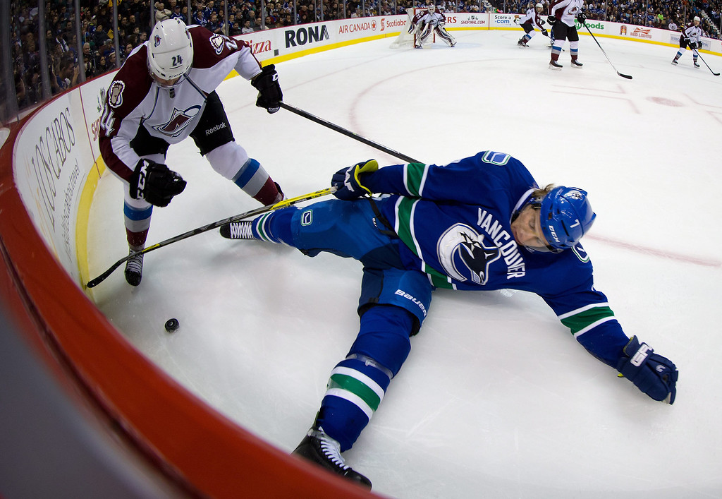 . Colorado Avalanche\'s Marc-Andre Cliche, left, checks Vancouver Canucks\' David Booth to the ice during first period NHL hockey game in Vancouver, British Columbia on Sunday, Dec. 8, 2013. (AP Photo/The Canadian Press, Darryl Dyck)