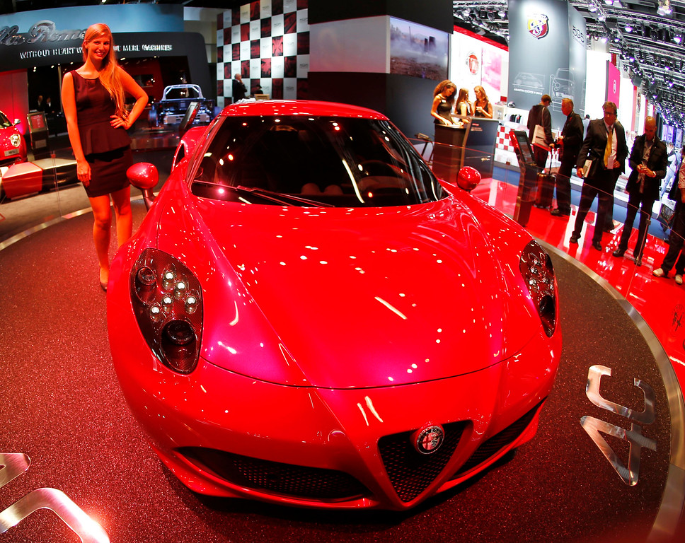 . A hostess stands next to a Alfa Romeo 4 C during the first press day of the 65th Frankfurt Auto Show in Frankfurt, Germany, Tuesday, Sept. 10, 2013. (AP Photo/Michael Probst)