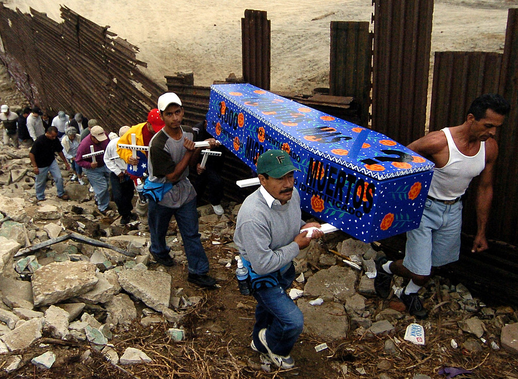 . Marchers carry a casket along a section of the U.S.-Mexico border fence in Tijuana, Mexico Friday, Oct. 1, 2004, to mark the 10th anniversary of the U.S. border enforcement program Operation Gatekeeper. Immigrants rights groups blame the program for immigrant deaths because the active enforcement in the Tijuana area drives illegal immigrants to try to cross the border in the rougher terrain to the east. The U.S. Border Patrol maintains that increased vigilance and other efforts have helped reduce deaths among illegal immigrants crossing the border. Migrants-rights groups contend the agency has tried to shave its count by excluding from its total many skeletal remains, car-accident victims and bodies discovered by local law enforcement agencies. (AP Photo/Denis Poroy, File)