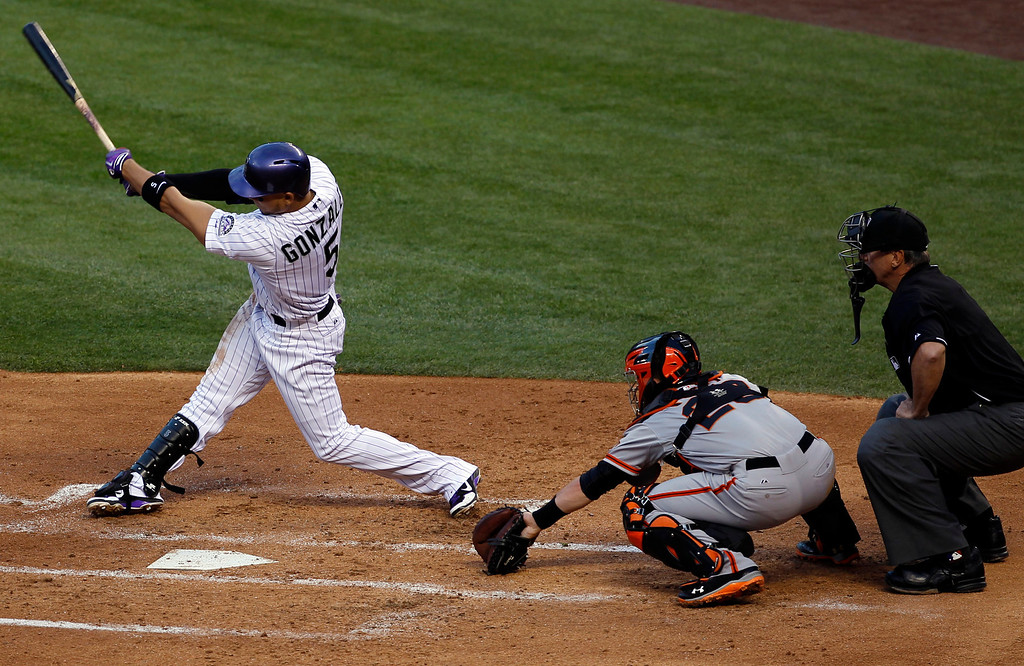 . Colorado Rockies\' Carlos Gonzalez, left, grounds out to drive in a run as San Francisco Giants catcher Buster Posey, center, and home plate umpire Tim McClelland look on in the third inning of a baseball game in Denver, Saturday, May 18, 2013. (AP Photo/David Zalubowski)