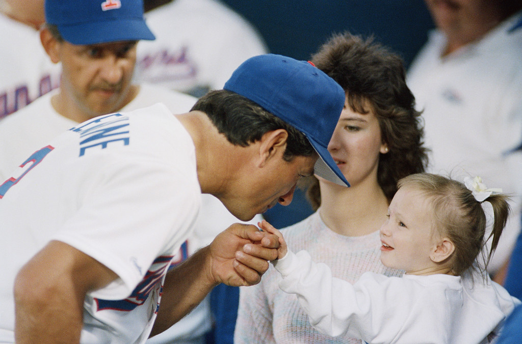 . Texas Rangers manager Bobby Valentine reaches to kiss two-year-old Jessica McClure on the hand before home opener against the Cleveland Indians in Arlington, Texas on Monday, April 4, 1988. Jessica, being held by her mother, \'Cissy\' attracted international attention last October when she trapped in a dry well in Midland, Texas for over 50 hours. Jessica threw out the first pitch of the game. (AP Photo/Ron Heflin)