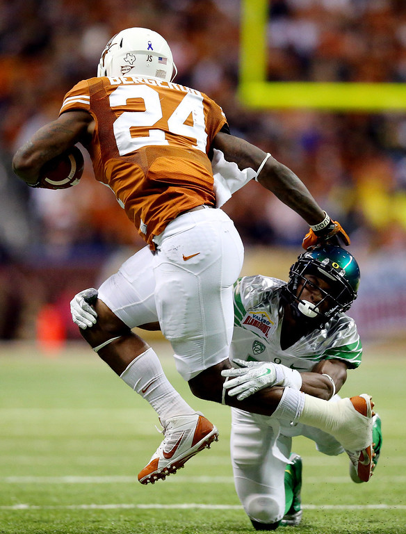 . Running back Joe Bergeron #24 of the Texas Longhorns tries to avoid a tackle by cornerback Ifo Ekpre-Olomu #14 of the Oregon Ducks  during the Valero Alamo Bowl at the Alamodome on December 30, 2013 in San Antonio, Texas.  (Photo by Ronald Martinez/Getty Images)