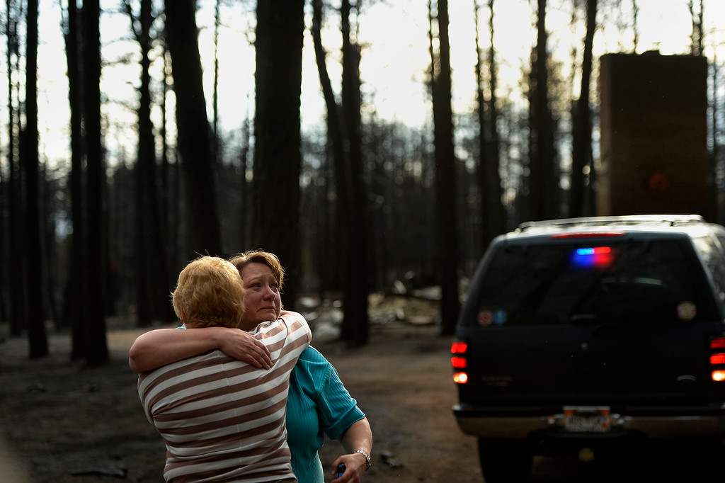 . Teresa Robertson breaks down into tears as she is hugged by a neighbor at her home that was totally taken by the fire as some residents were allowed back to see their homes in the Black Forest Fire area near Colorado Springs, Colorado. June 18, 2013. (Photo By Joe Amon/The Denver Post)