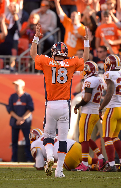 . Denver Broncos quarterback Peyton Manning (18) signals for a touchdown after Denver Broncos running back Montee Ball (28) ran it in during the third quarter. (Photo by John Leyba/The Denver Post)