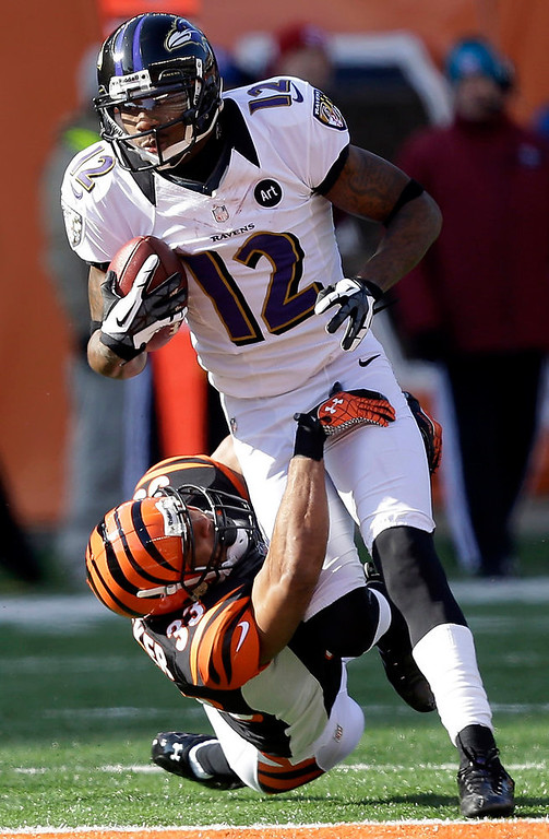 . Baltimore Ravens wide receiver Jacoby Jones (12) is tackled by Cincinnati Bengals strong safety Chris Crocker (33) after a short gain in the first half of an NFL football game on Sunday, Dec. 30, 2012, in Cincinnati. (AP Photo/Al Behrman)
