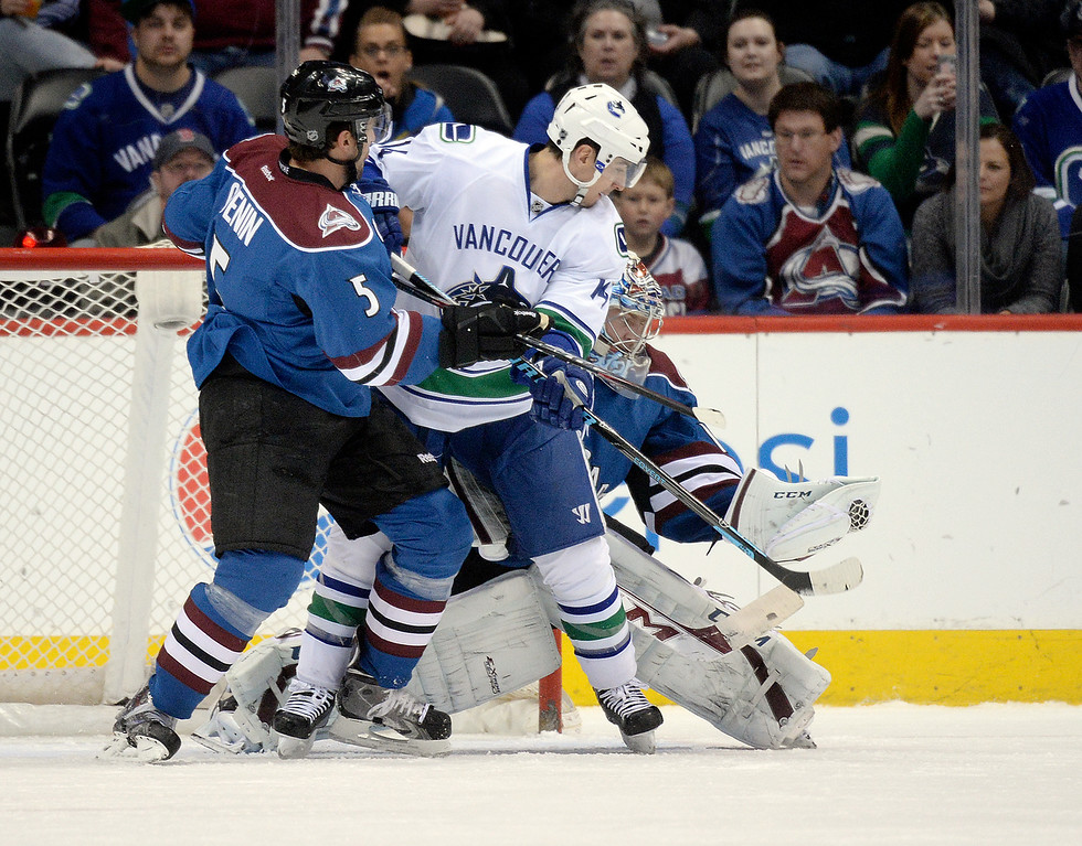 . Colorado goalie Semyon Varlamov made a glove save as defenseman Nate Guenin (5) battled with Vancouver wing Alexandre Burrows (14) in the crease in the first period. The Colorado Avalanche hosted the Vancouver Canucks Thursday night, March 27, 2014 at the Pepsi Center in Denver, Colorado. (Photo by Karl Gehring/The Denver Post)